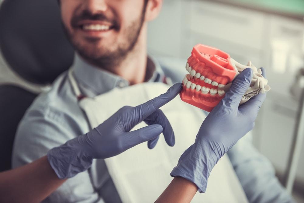 Le déchaussement des dents, aussi appelé récession gingivale, survient lorsque la gencive qui entoure la dent se dégrade. La dent perd ainsi de sa protection naturelle et comme elle se trouve exposée, elle devient plus sensible. De plus, le déchaussement étant progressif, il peut mener à un affaiblissement du support osseux de la dent qui pourrait se mettre à trembler et qui pourrait même tomber. Ce problème, qui touche de nombreuses personnes, peut néanmoins se prévenir et se traiter. L'équipe de la Clinique du Dr David Côté est qualifiée pour diagnostiquer le déchaussement des dents et pour prodiguer le traitement approprié. Seulement, il est important de comprendre ses causes et ses symptômes afin de l'identifier rapidement. Causes Le déchaussement est lié à une inflammation des gencives et peut avoir plusieurs causes. - L'accumulation de plaque dentaire, due à une mauvaise hygiène bucco-dentaire; - Le bruxisme; - L'utilisation de la mauvaise brosse à dents (dont les soies sont trop dures); - L'hérédité; - Un mauvais alignement des dents; - Des traitements orthodontiques inappropriés; - Le stress; - Le diabète; - La cigarette et le tabac; Symptômes Le déchaussement se manifeste de plusieurs manières et peut affecter la sensibilité des dents et gencives, de même que leur aspect visuel : - L'impression, lorsque vous les comparez, qu'une ou plusieurs dents sont plus allongées que les autres. - Une enflure ou une rougeur persistante des gencives ou des saignements récurrents lors du brossage des dents. - L'accroissement de la sensibilité des dents lorsqu'elles sont en contact avec le chaud, le froid ou des aliments acides. Traitements Cette condition peut néanmoins être traitée afin d'éviter qu'elle ne s'aggrave, de même que pour en contrôler les conséquences. Les traitements varieront selon la gravité du problème et le moment de sa prise en charge. Interventions mineures (lorsque le problème est pris dans sa phase précoce) : - Un nettoyage complet; cette interventio